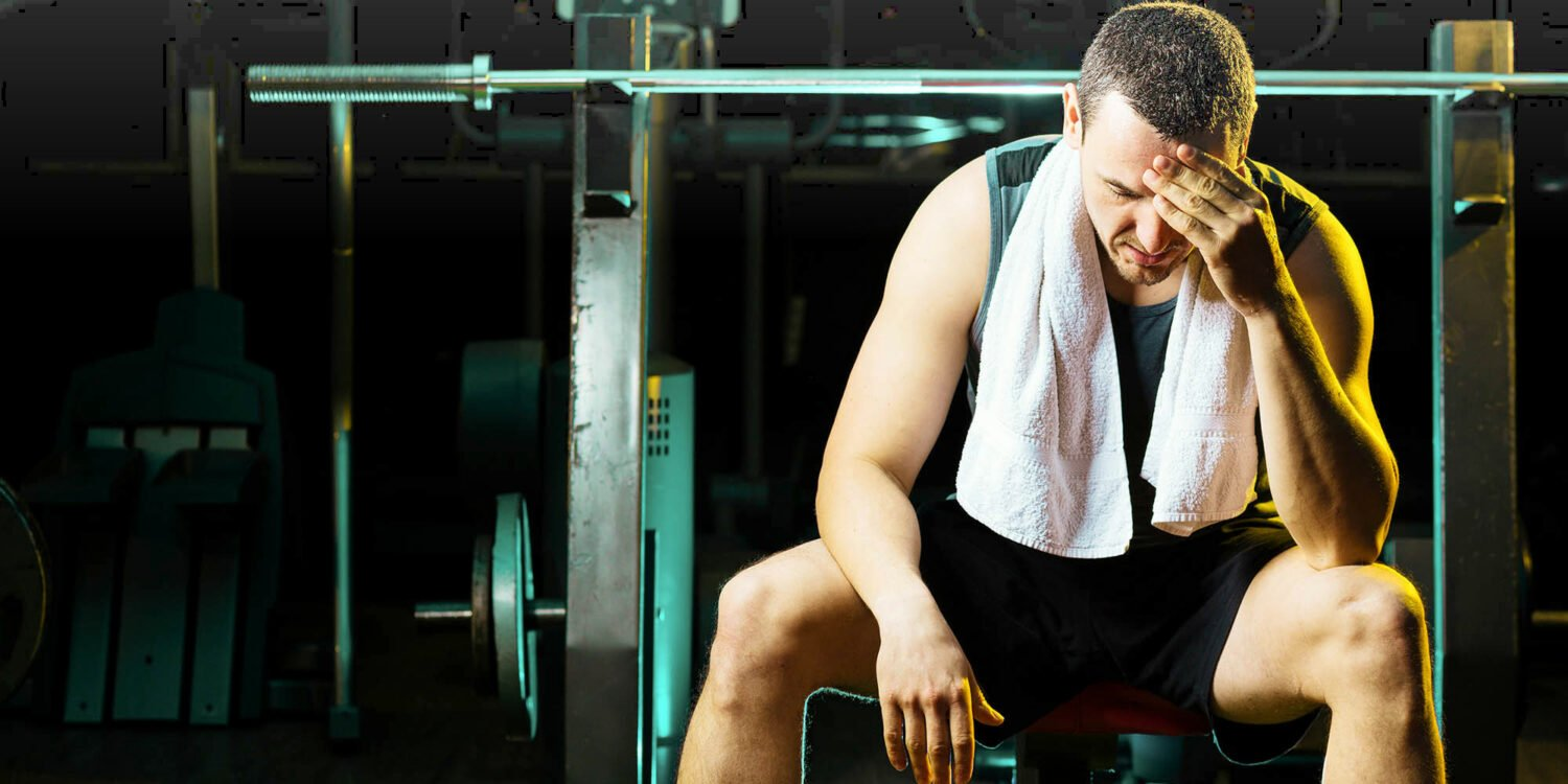 man sitting on a workout bench in a gym having dizziness