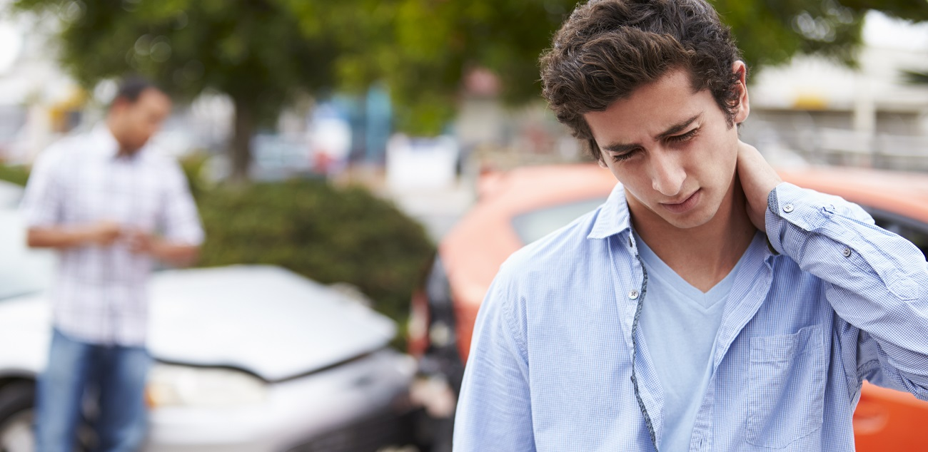 young man holding his neck in pain after whiplash due to a car accident