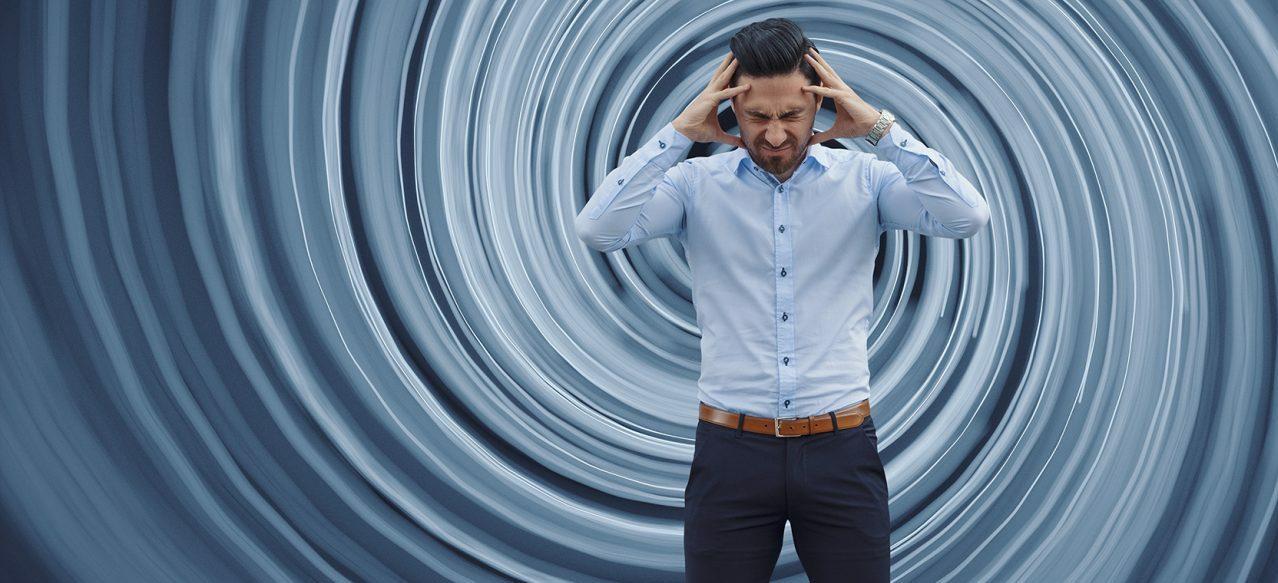 man suffering from vertigo holding his head in discomfort