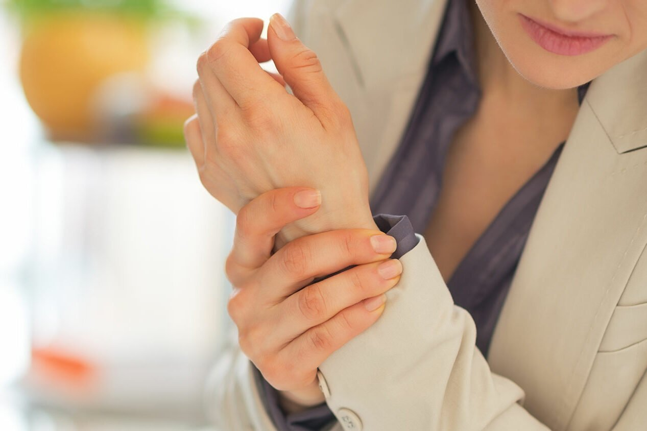 female holding her left wrist in pain due to carpal tunnel syndrome