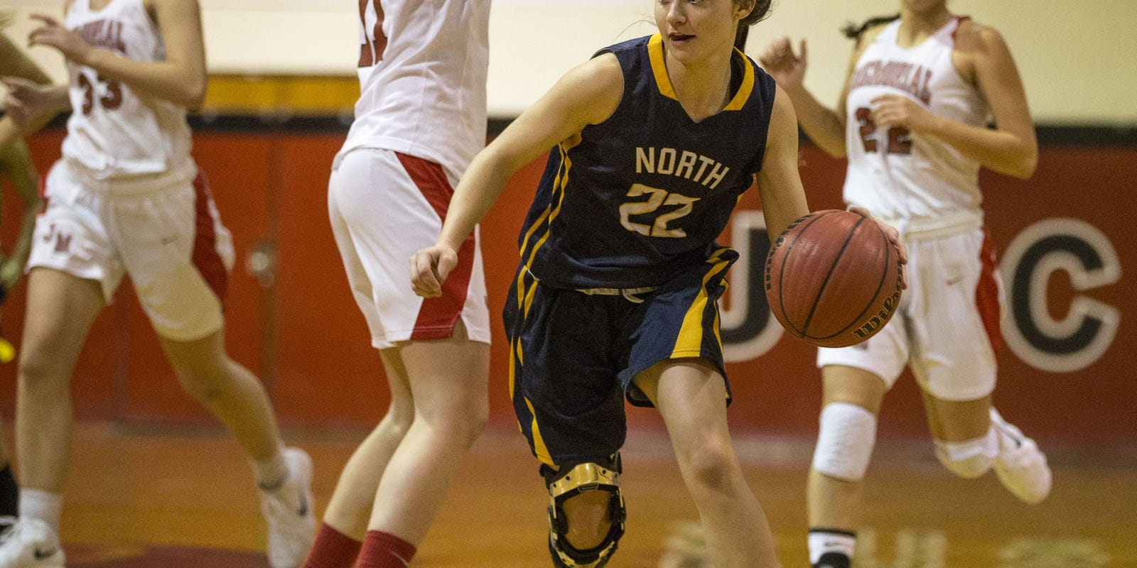 female basketball player with a knee brace dribbling the ball