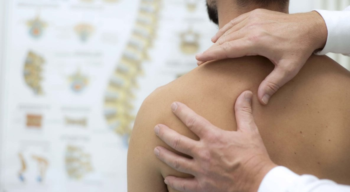 Rear view of a man having his left shoulder examined
