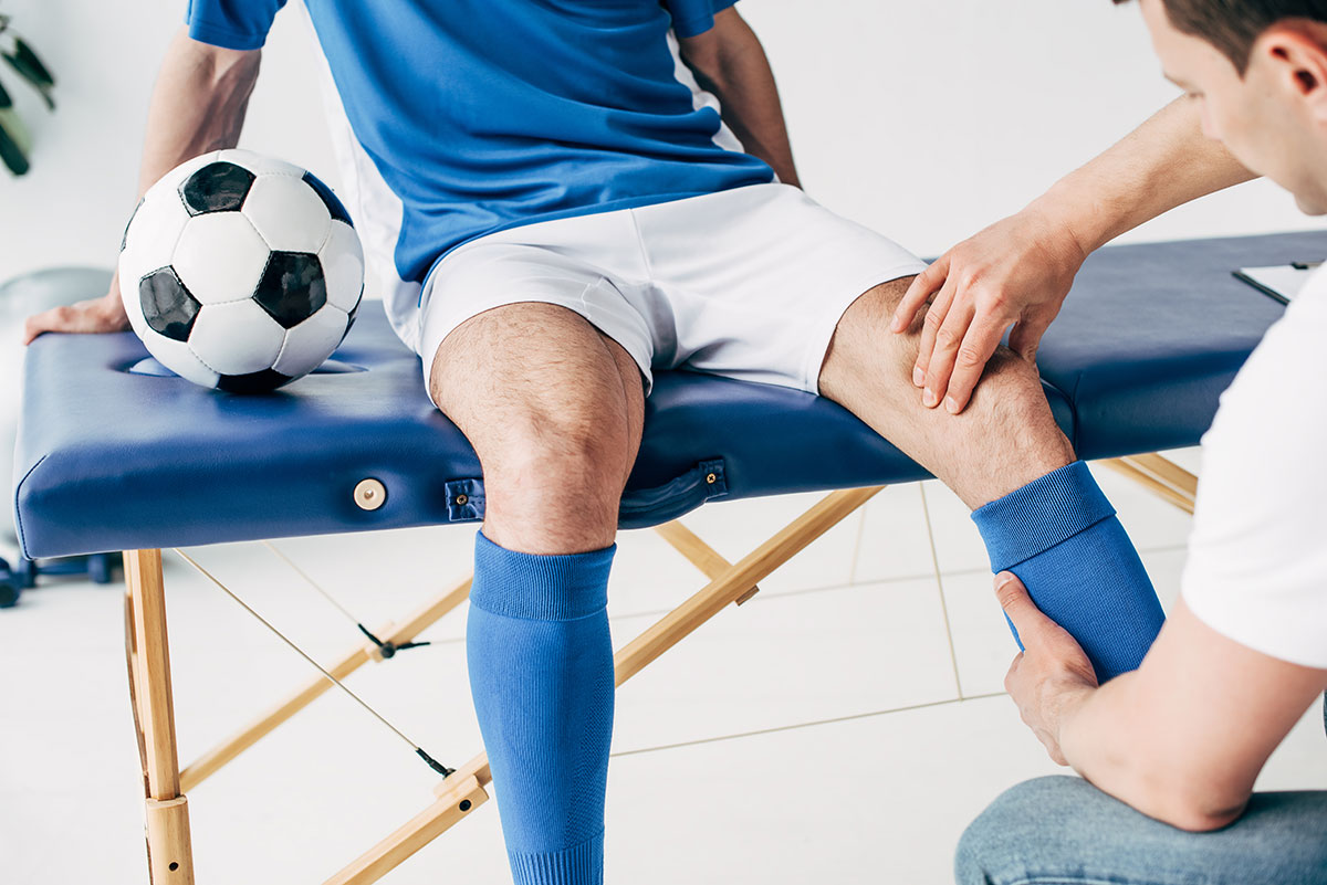 Physiotherapist examining the left knee of a soccer player in a clinic