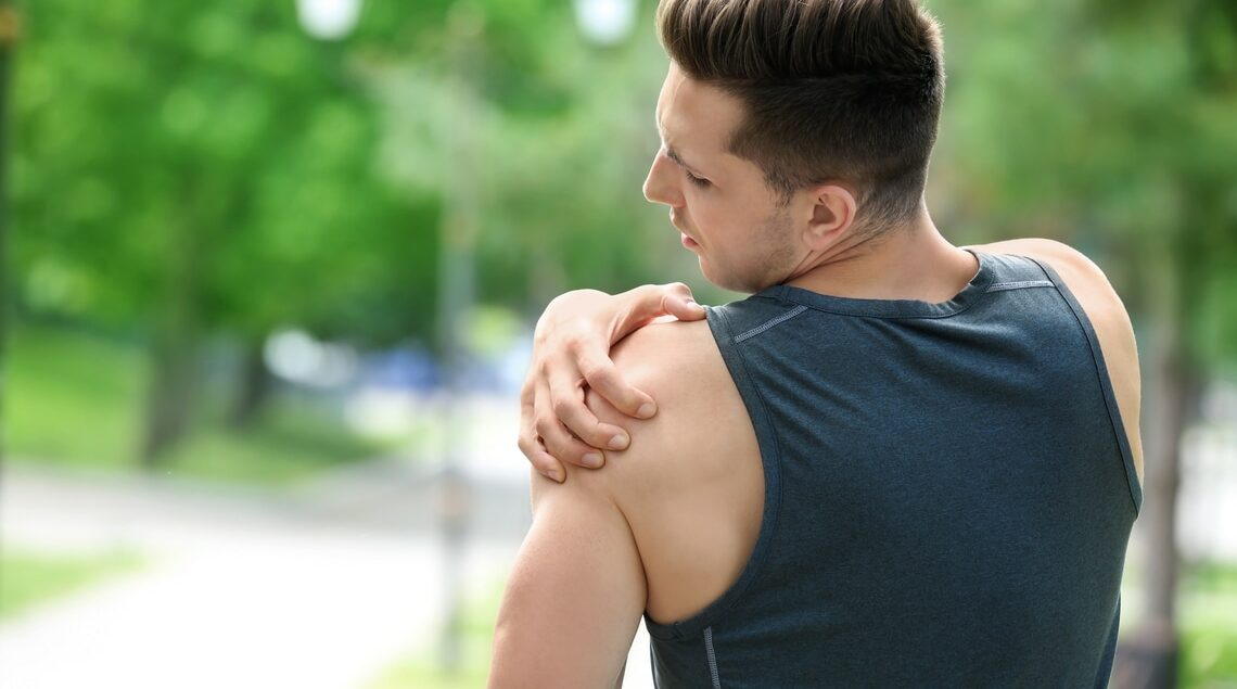Athletic man grabbing left rotator cuff area because of pain