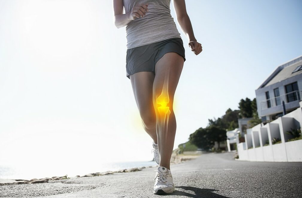 A woman jogging toward us on a seaside path with pain indicated around the left patella
