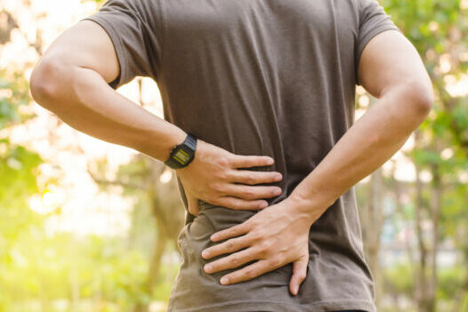 View of the back of a man standing and holding his low back in pain