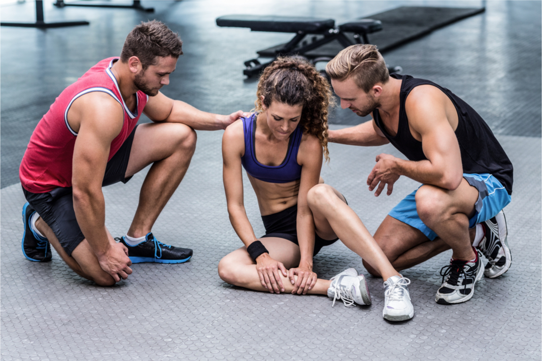 Woman sitting on the gym floor examining her right lower leg while concerned friends try to help