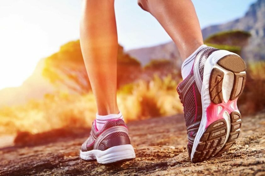 Cropped photo of the lower legs of a person wearing athletic shoes and walking outdoors