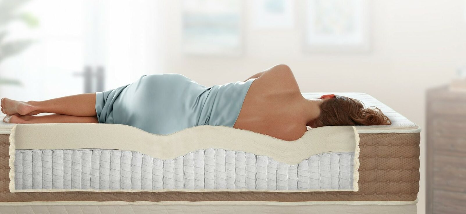 Woman lying on her side on a mattress showing how the mattress conforms well to the shape of her body