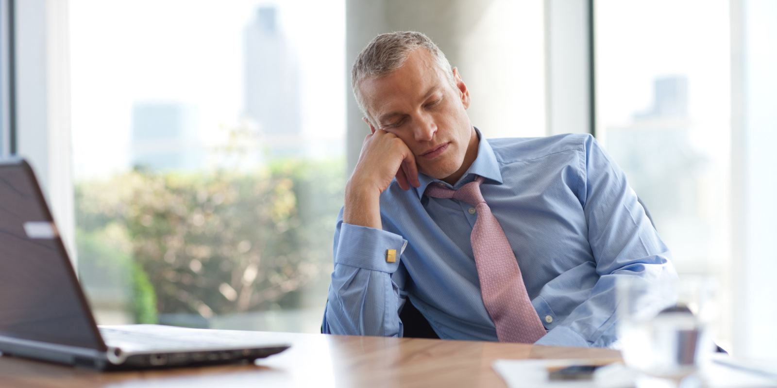 Man in business attire falling asleep at a desk