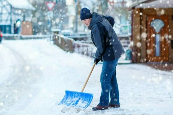 Man shoveling snow off of a walkway in front of a store