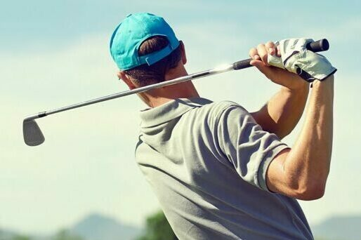 Man in the follow through phase of his golf swing