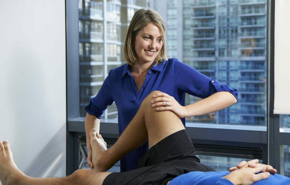Physiotherapist Courtney Steele performing knee joint mobilization on a patient at Cornerstone Physiotherapy North York