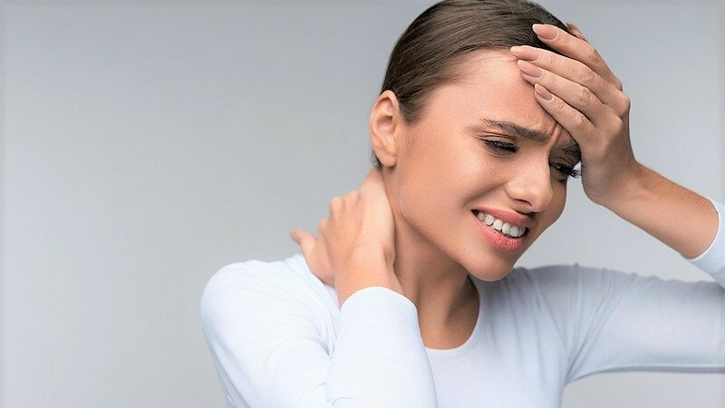 Woman grimacing from pain while holding her forehead and neck