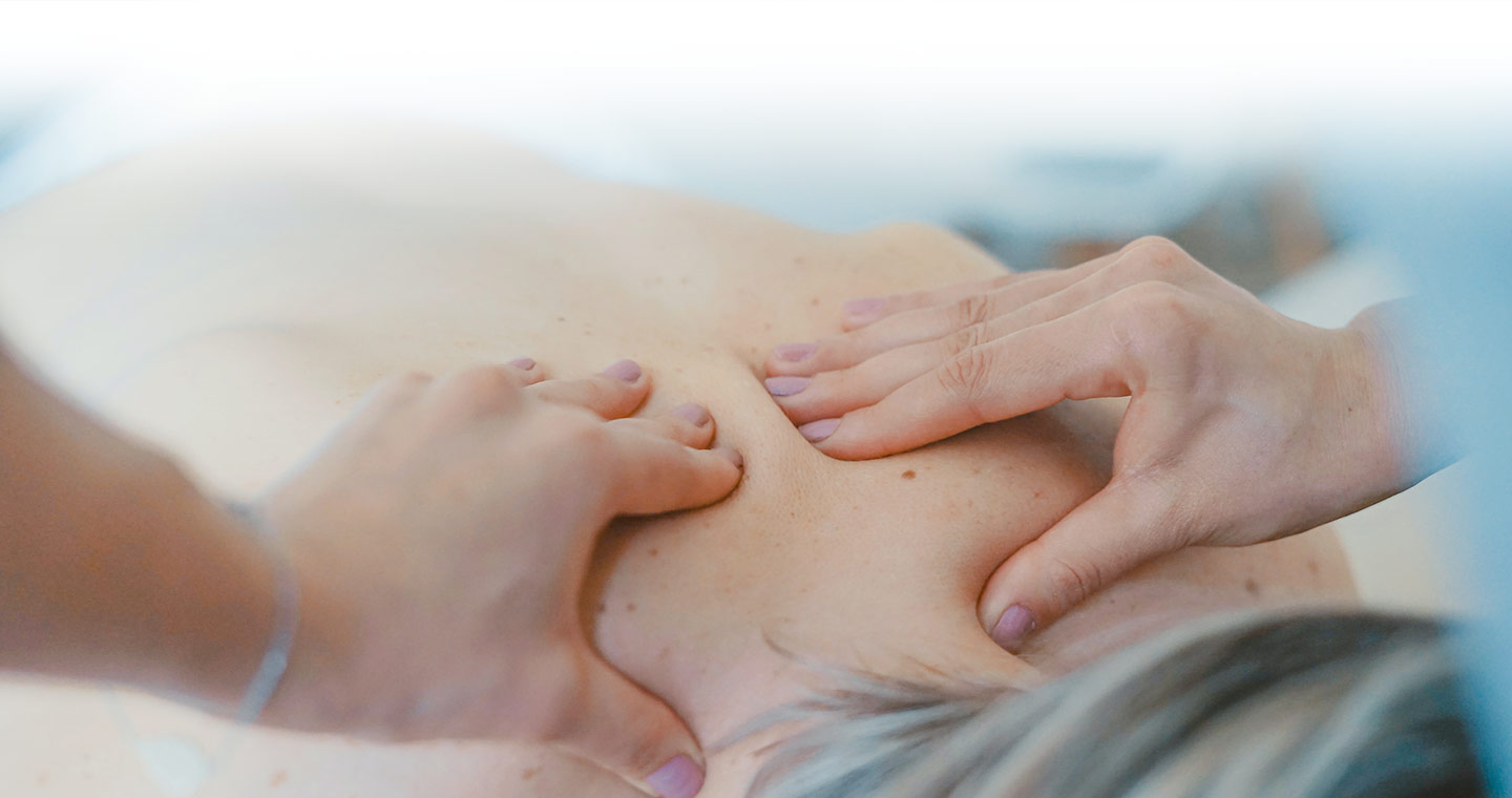 Close up of hands massaging a patients upper back