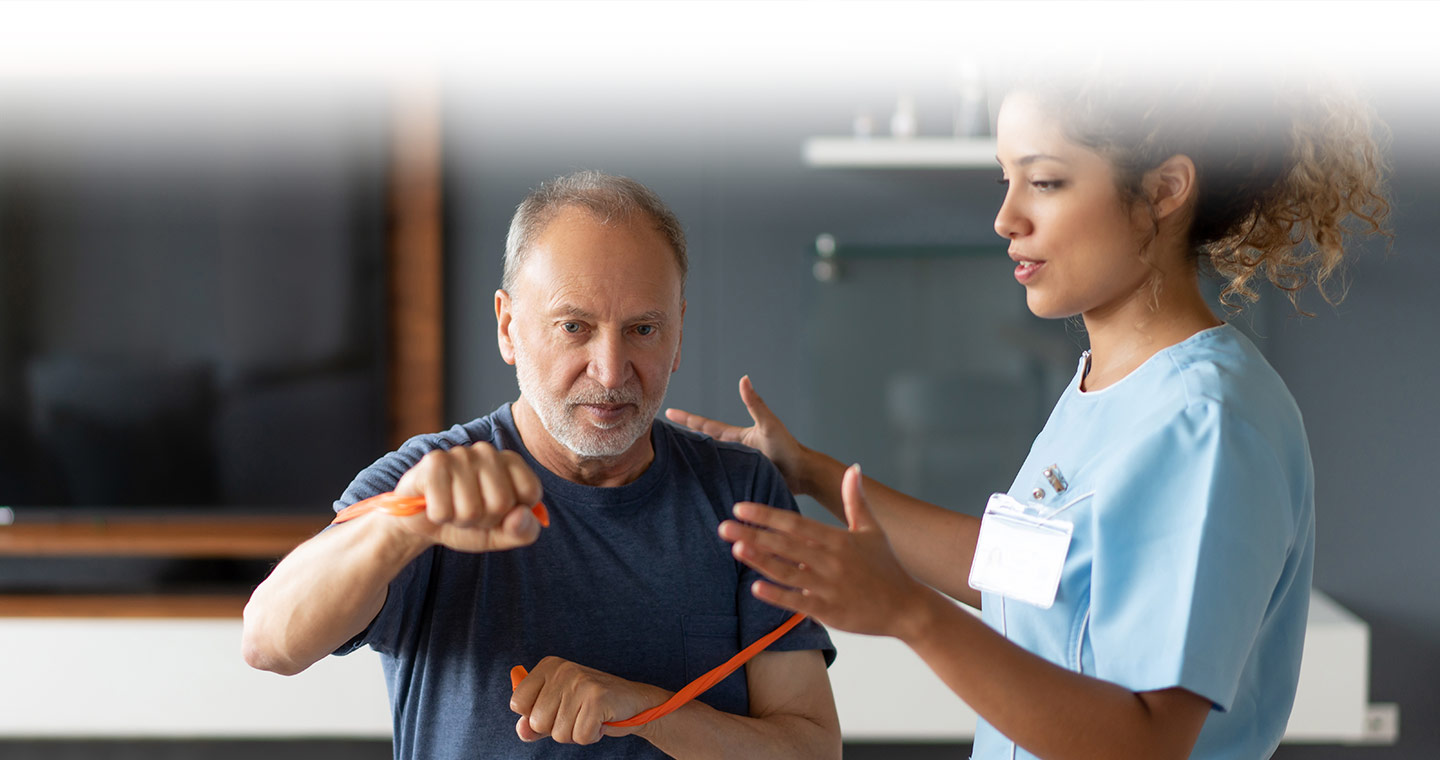 Man receiving exercise instruction from his physiotherapist while using a red resistance band