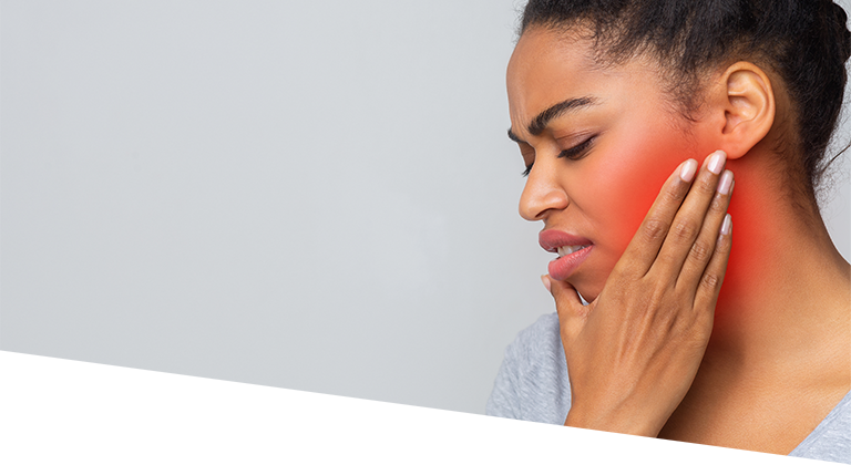 woman hold her jaw in pain due to TMJ syndrome