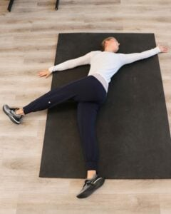 young woman lying in the end position of an eagle stretch, with arm spread apart and one leg flexed up