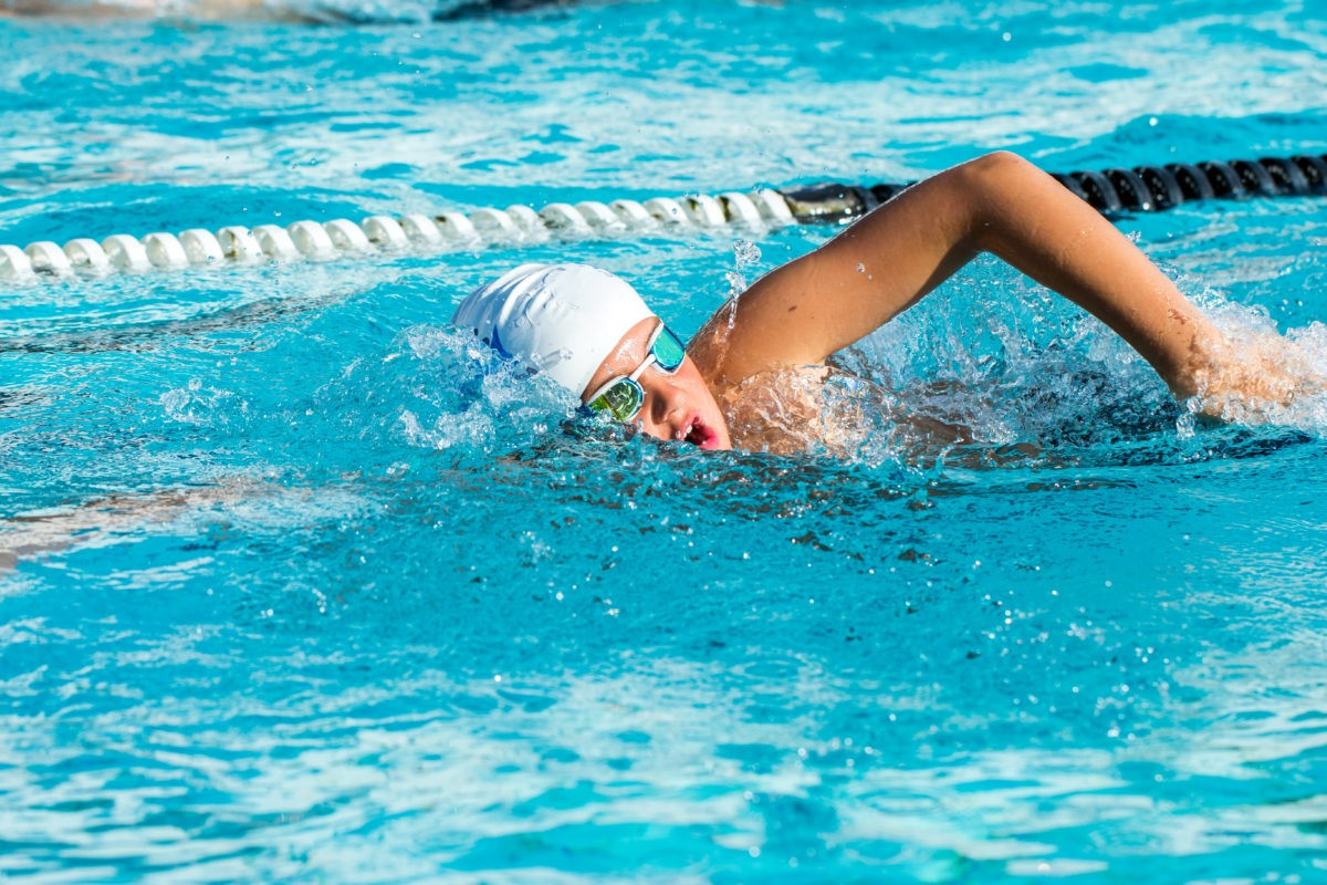 Young man performing freestyle swim training