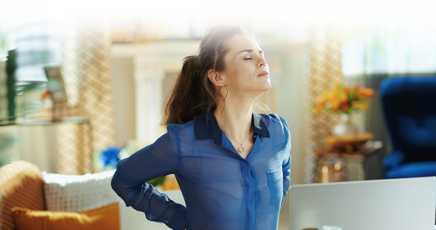 Woman sitting at a desk stretching her low back