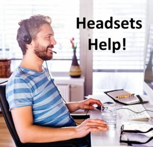 man sitting at a desk in front of a computer using a headset