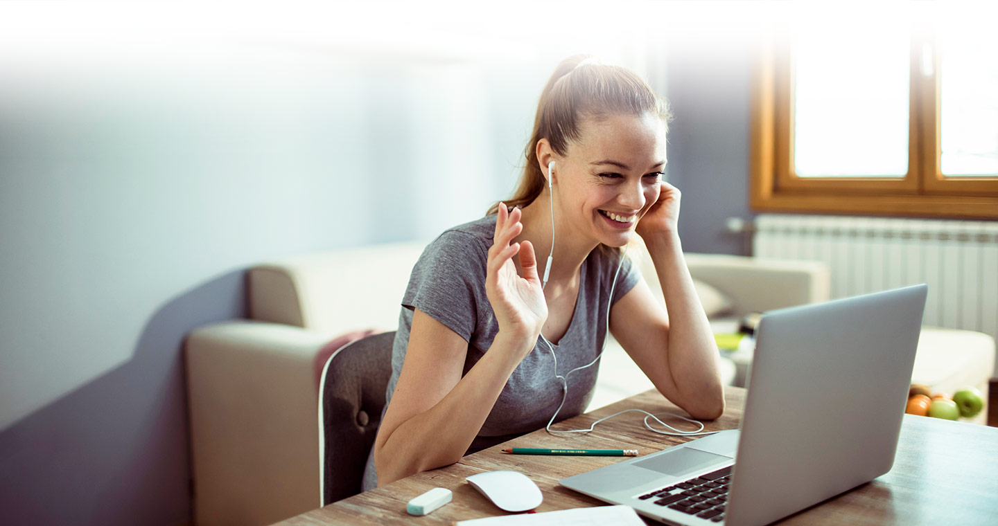 Woman happy and waving at a computer screen during a telehealth physiotherapy appointment online