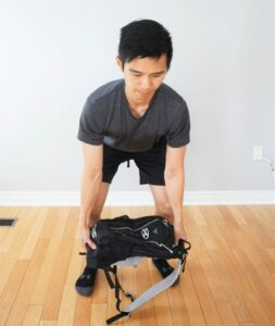 man bending forward in a dead-lift position preparing to lift a heavy backpack