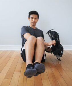 man seated on the floor holding a heavy backpack to his side ready to lift