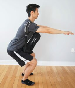 man performing a squat while wearing a heavy backpack across his chest