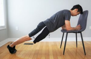 man performing a plank exercise with upper body elevated on a chair