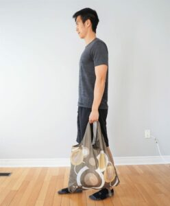 man performing a farmer's walk exercise lifting a heavy bag with one arm
