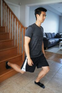 man performing a split squat coming down from stairs