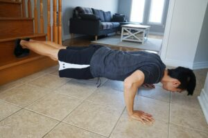 man performing a push up exercise with feet on first step of stair