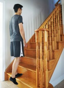 man performing a step up exercise on stairs