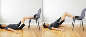 man performing a bridging exercise with feet resting on a chair