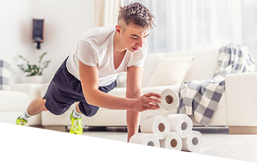 Young man in a plank exercise position stacking rolls of toilet paper into a pyramid