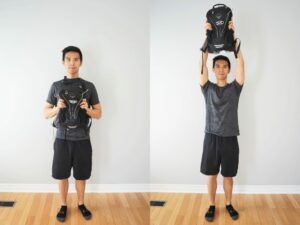 man using a backpack to perform a shoulder press exercise