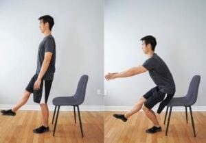 man performing a single leg squat with a chair behind him