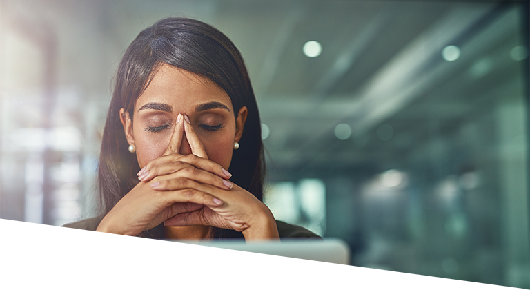 Woman sitting in front of computer stressed out with eyes closed and hands on her face