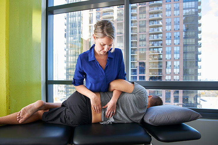 Clinic Director Courtney Steele performing advanced manual therapy techniques to treat low back pain.