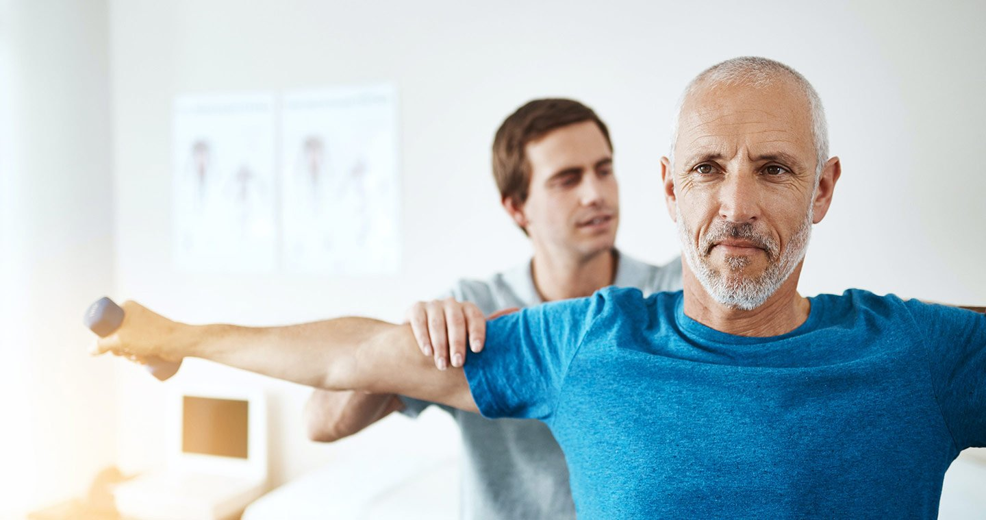 Man performing shoulder exercises while a physiotherapist treats him