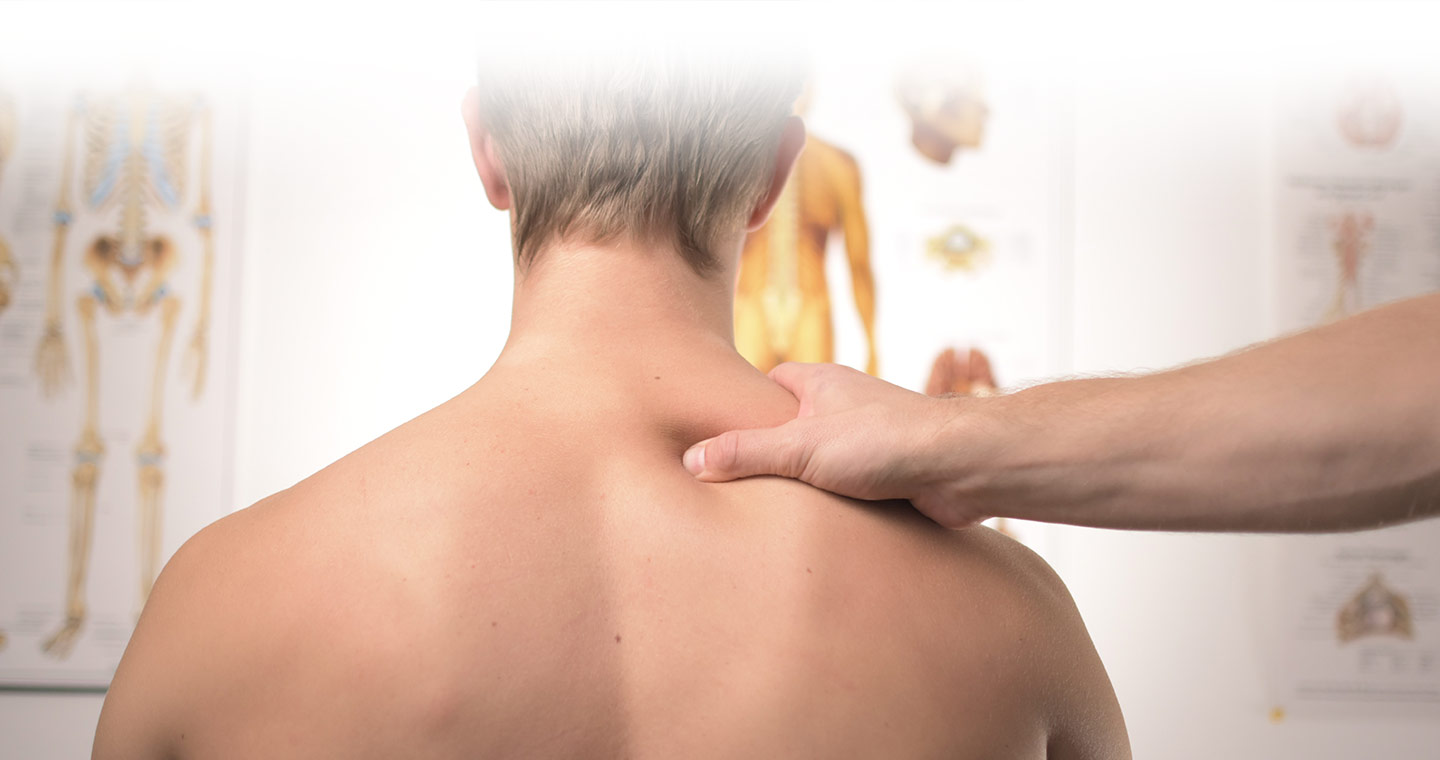 man's back with a hand massaging his right shoulder trapezius muscle