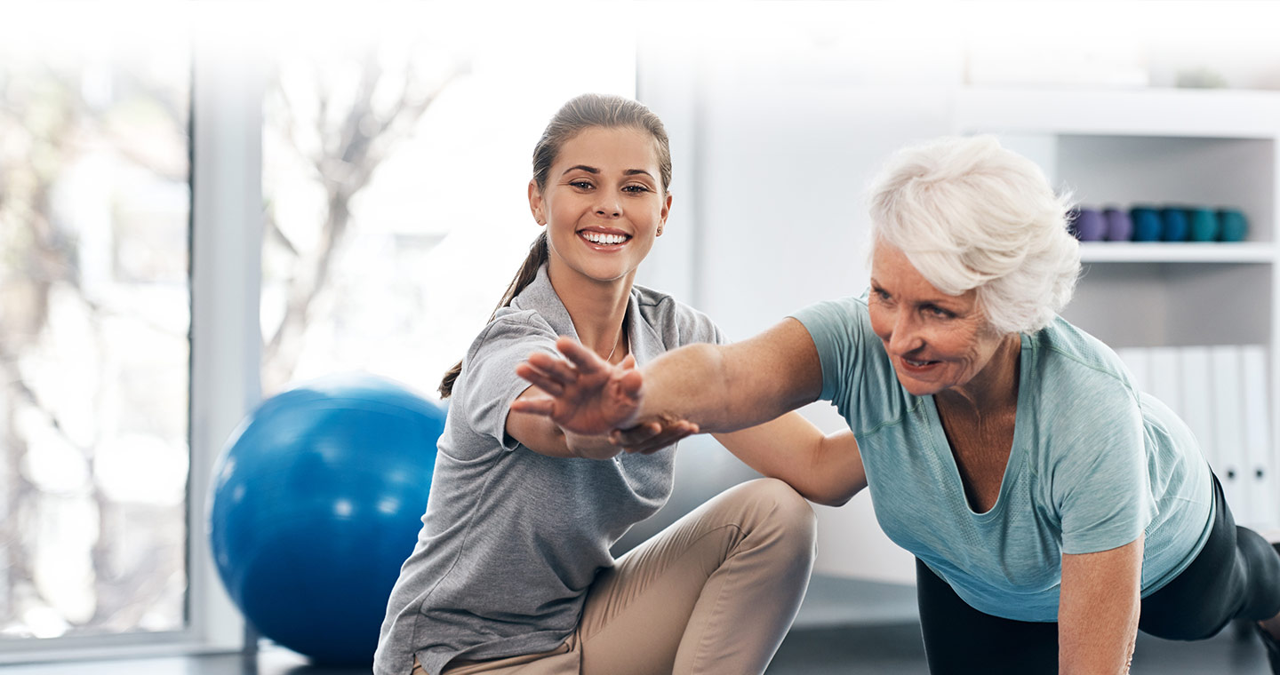 Older woman receiving instruction on a bird dog core exercise from her physiotherapist
