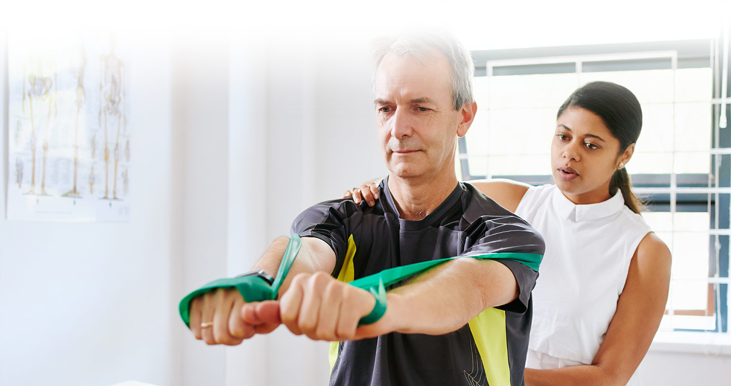 Man performing a shoulder exercise with a resistance band while physiotherapist provides instruction