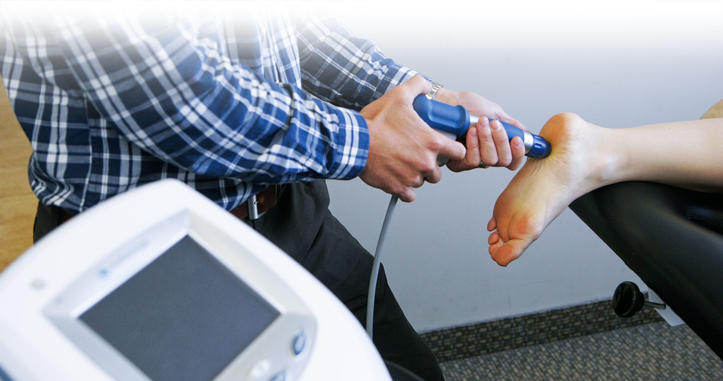 Physiotherapist Adam Brown Applying shockwave therapy to a patients plantar fasciitis