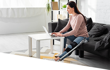 Woman with a leg injury participating in a virtual physiotherapy consultation from home