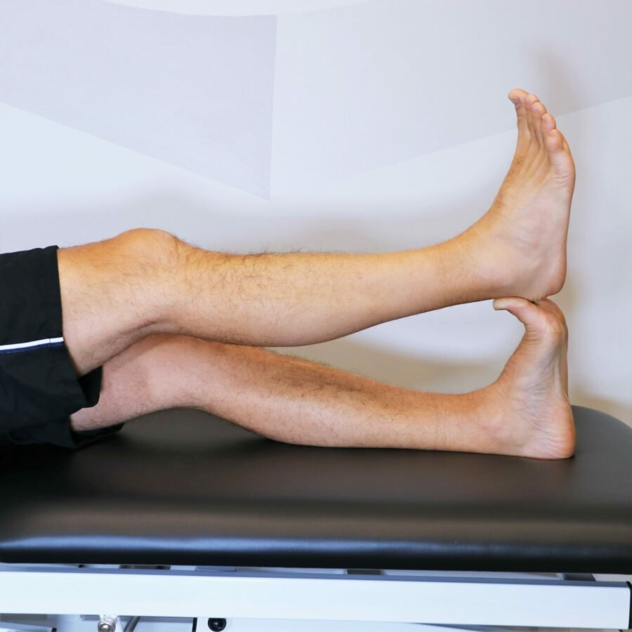 legs shown in a lying position with one leg being used to stretch the plantar fasciia of the other leg