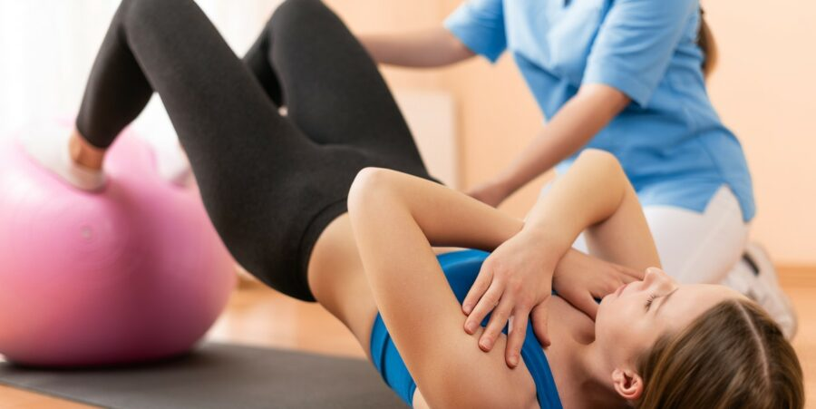 young woman performing a pelvic bridge exercise with feet on a yoga ball supervised by a physiotherapist