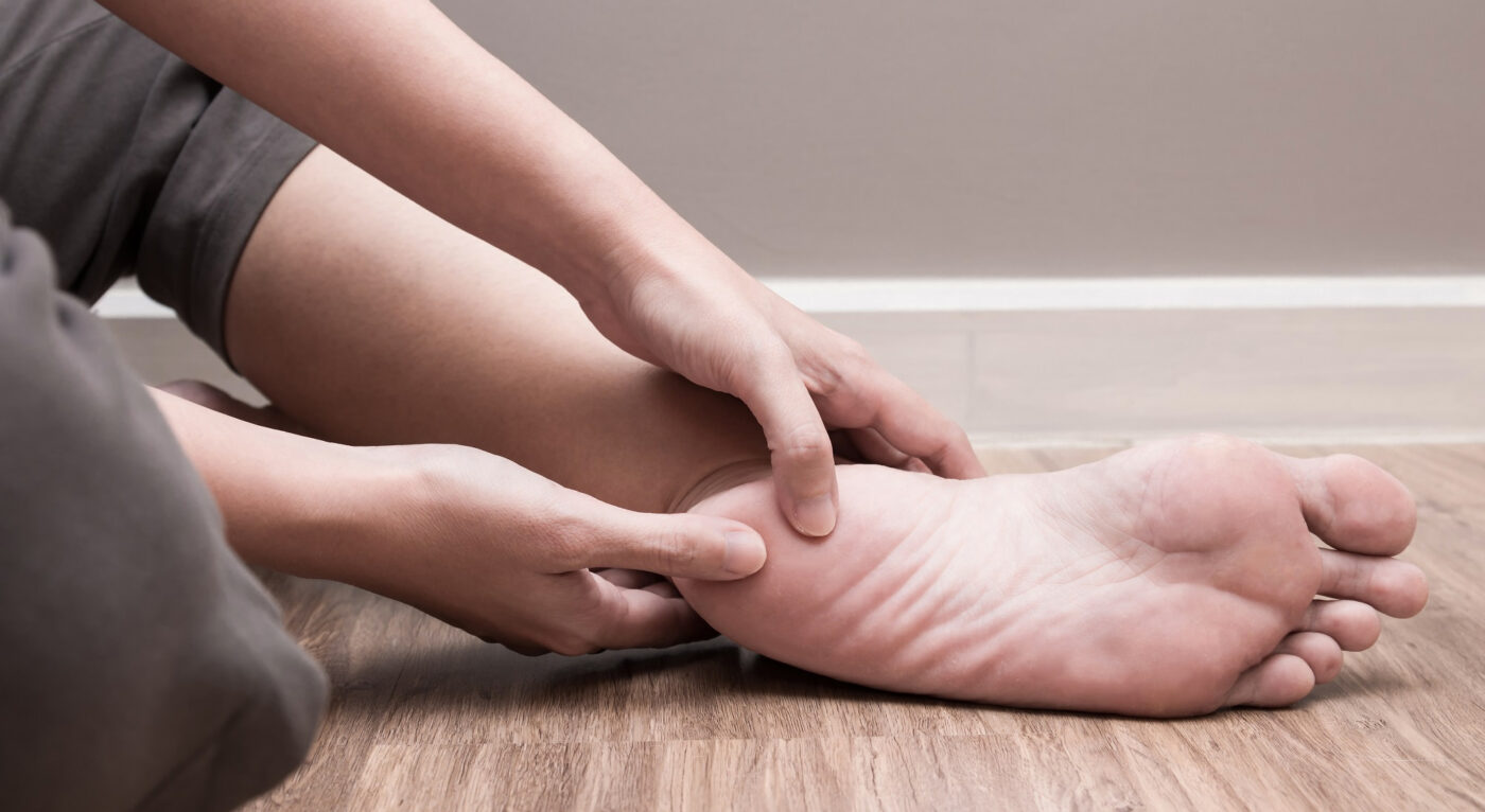 personal holding her heel in pain due to plantar fasciitis