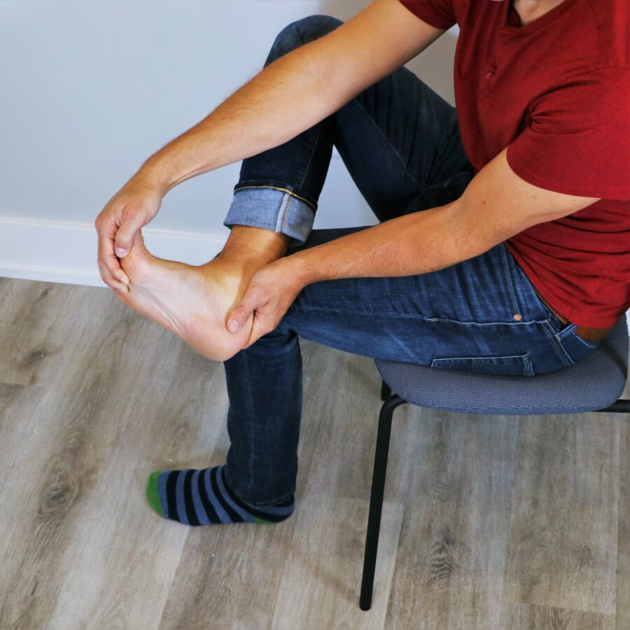 man holding foot while performing a sitting plantar fasciitis stretch in a chair
